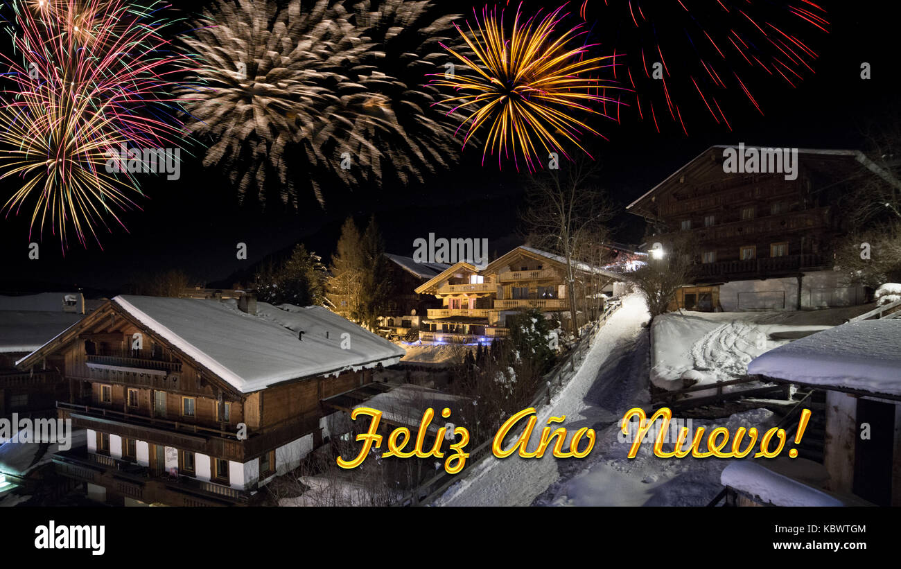 new year's eve card with alpine village in snow, fireworks, text 'Feliz Ano Nuevo!' - Stock Image