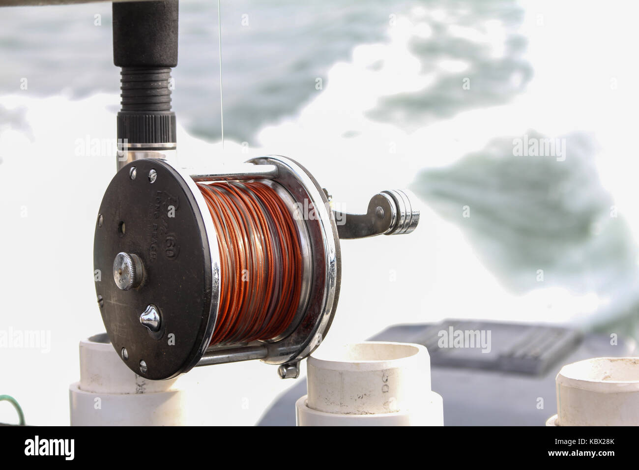 Close up of a lead core fishing reel in a rod holder on a boat that is moving through the water. - Stock Image