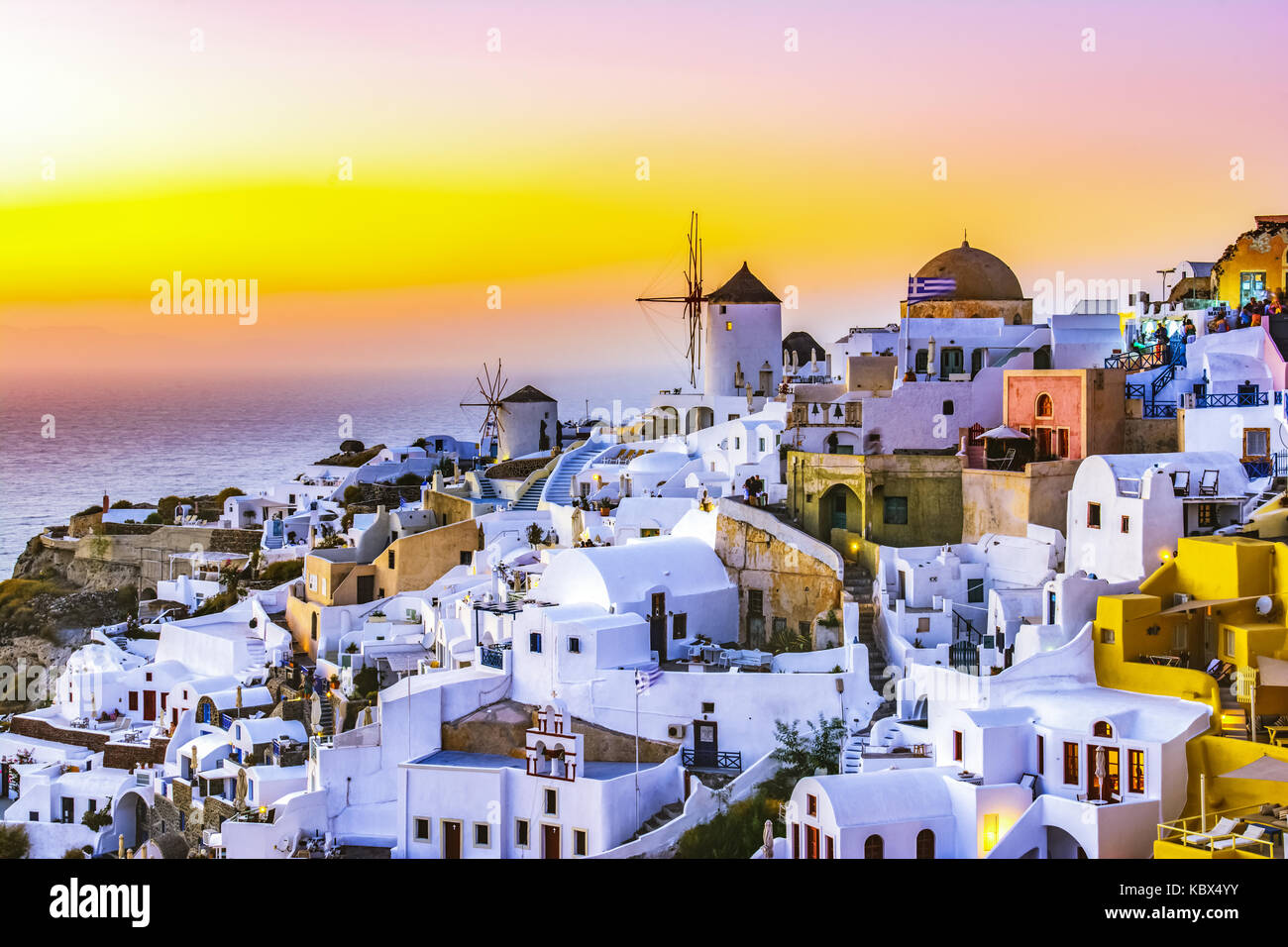 Sunset in Oia town, Santorini island, Greece. Traditional and famous white houses and churches  with blue domes - Stock Image