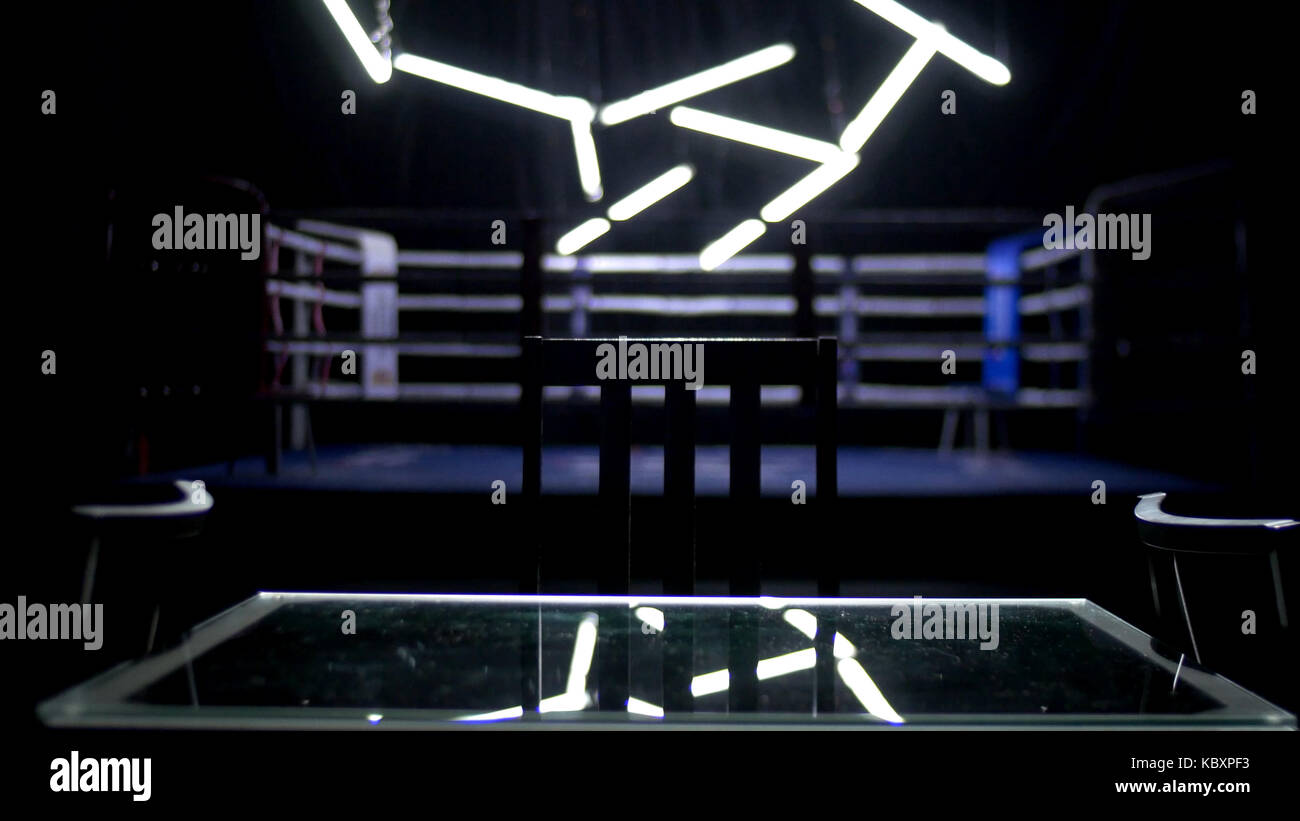 Boxing ring and two chairs with table dark background. View of a regular boxing ring surrounded by blue ropes spotlit - Stock Image