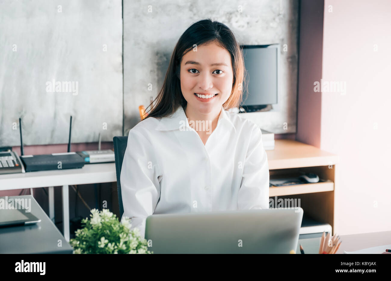Asian businesswoman working with laptop computer on desk with smiling face,Happy office life concept,working woman - Stock Image