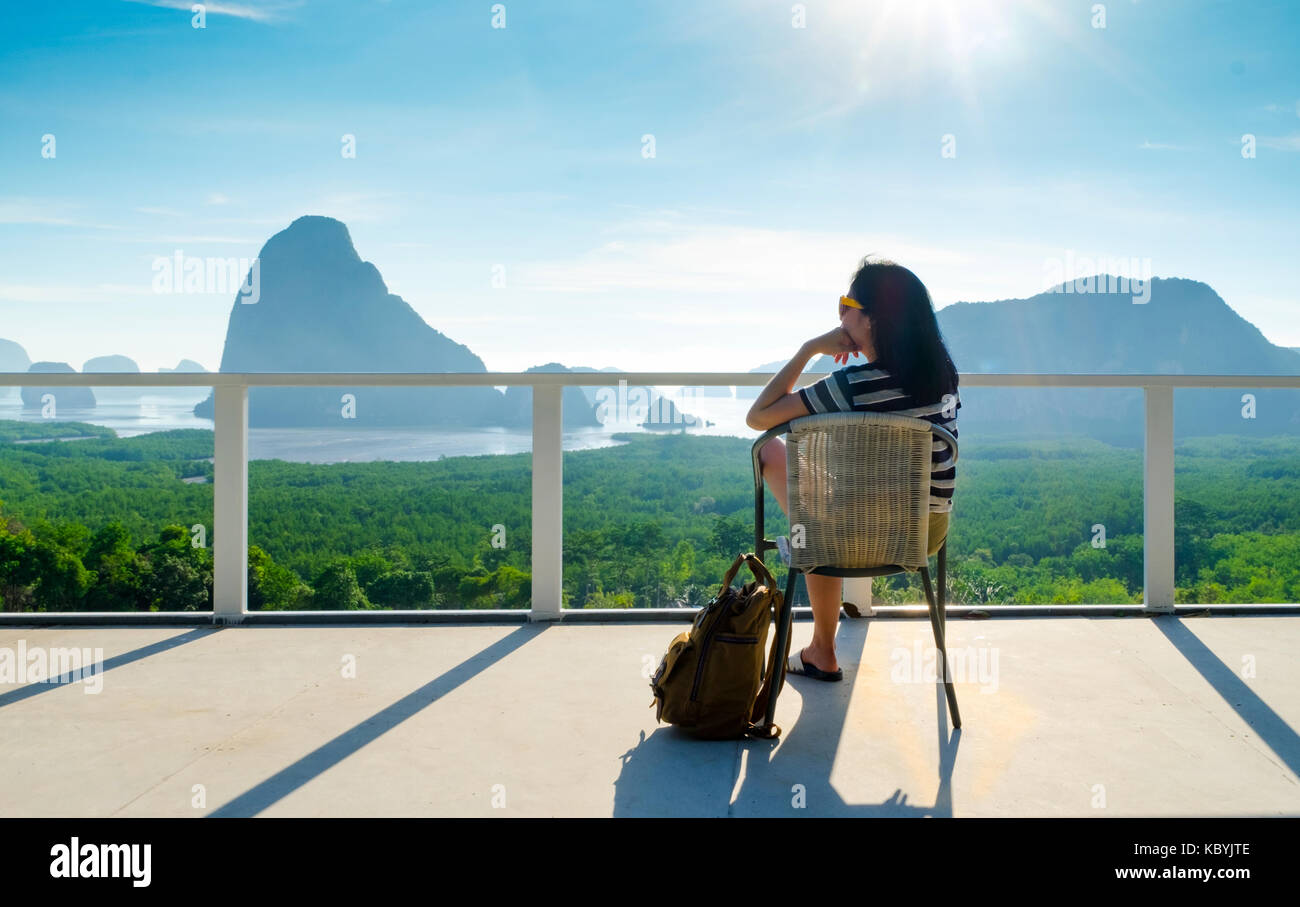 Young traveler woman backpacker sitting at chair and enjoying a beautiful of nature at mountain panorama view point - Stock Image
