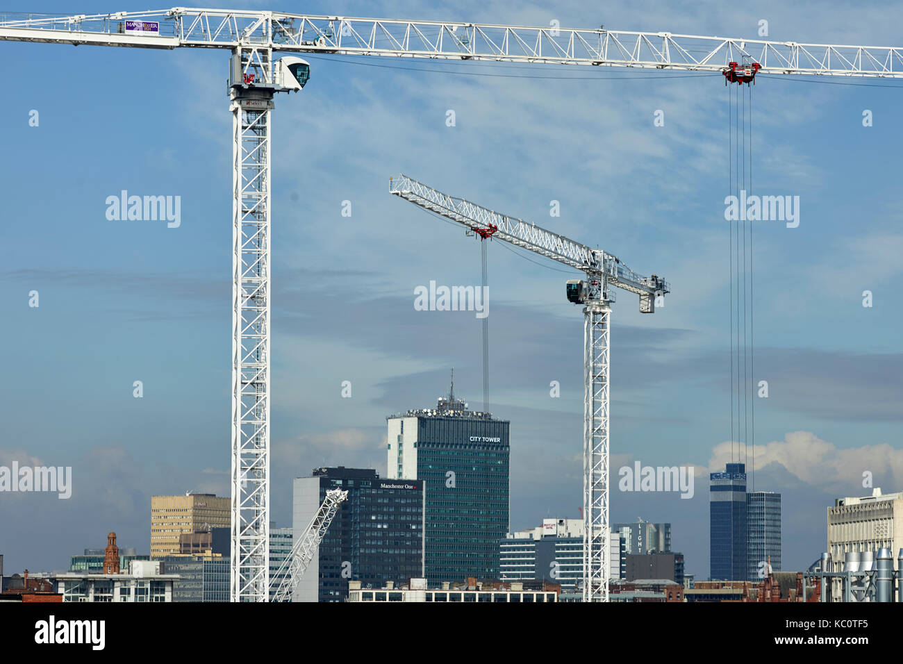 Manchester city centre skyline frames by tower cranes - Stock Image