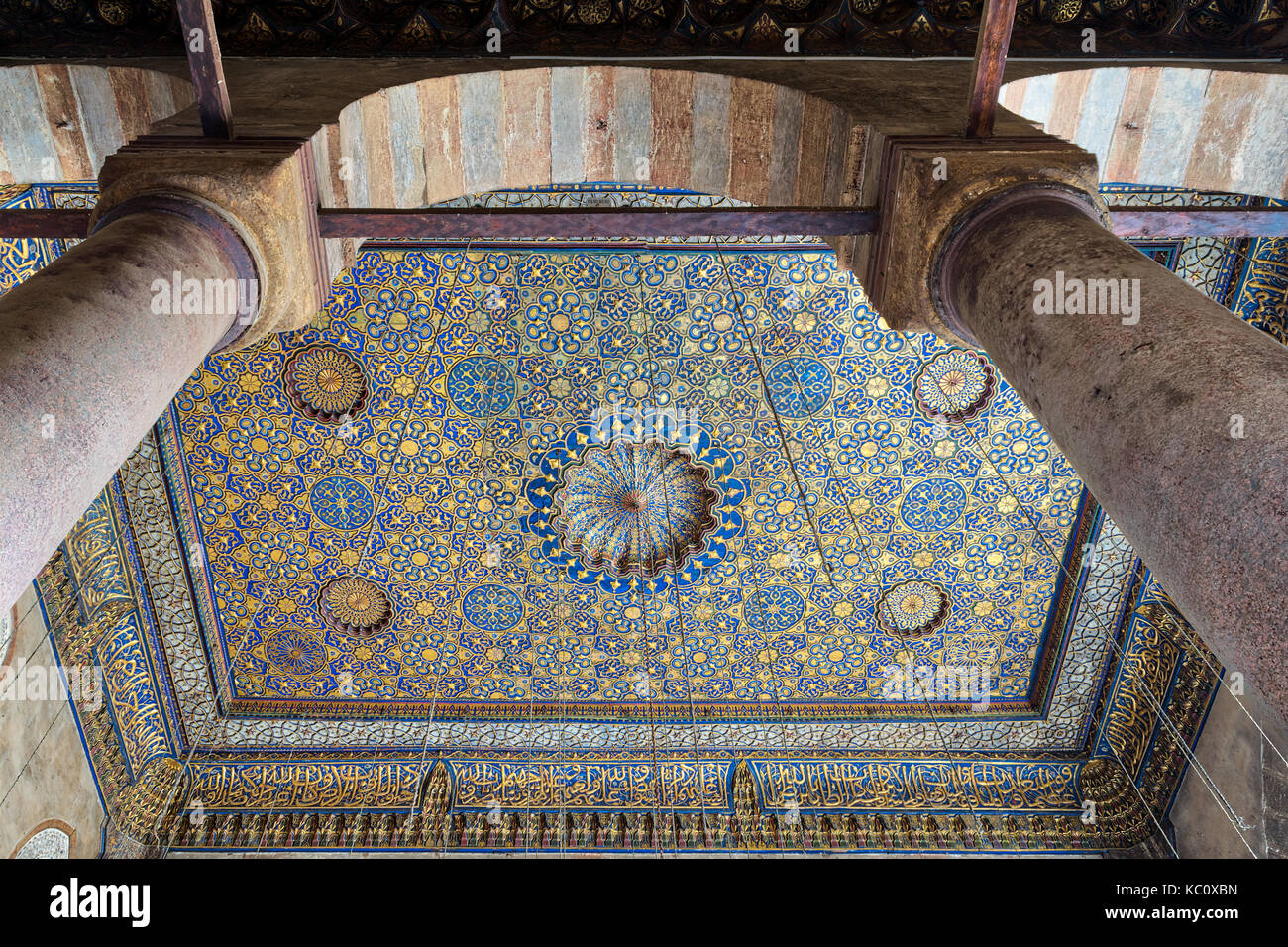Ornate ceiling with blue and golden floral pattern decorations frammed throught huge arch and two columns at Sultan - Stock Image