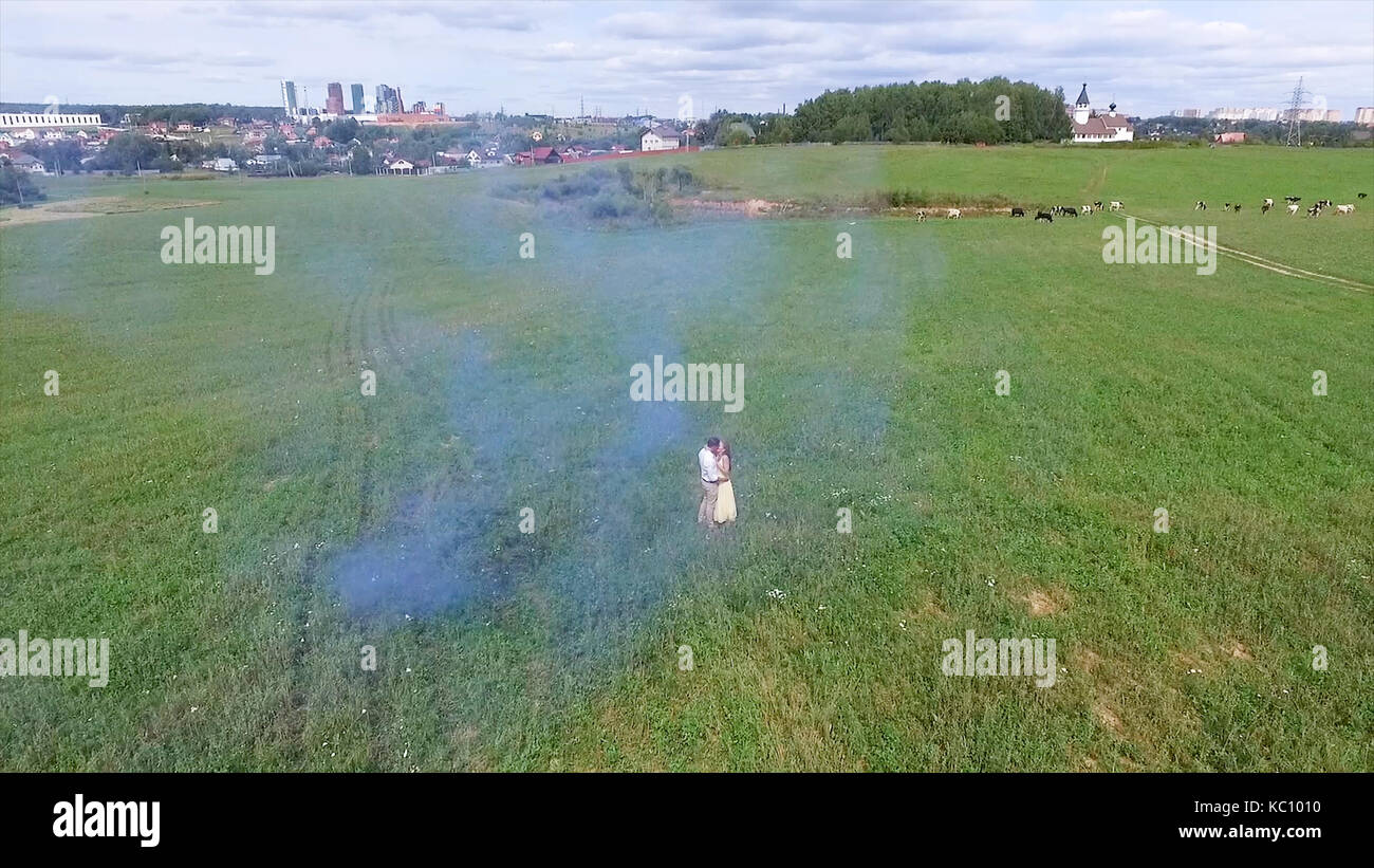Aerial survey of couple walk on the field with colored smoke in hands. Flying over man and woman run through the - Stock Image
