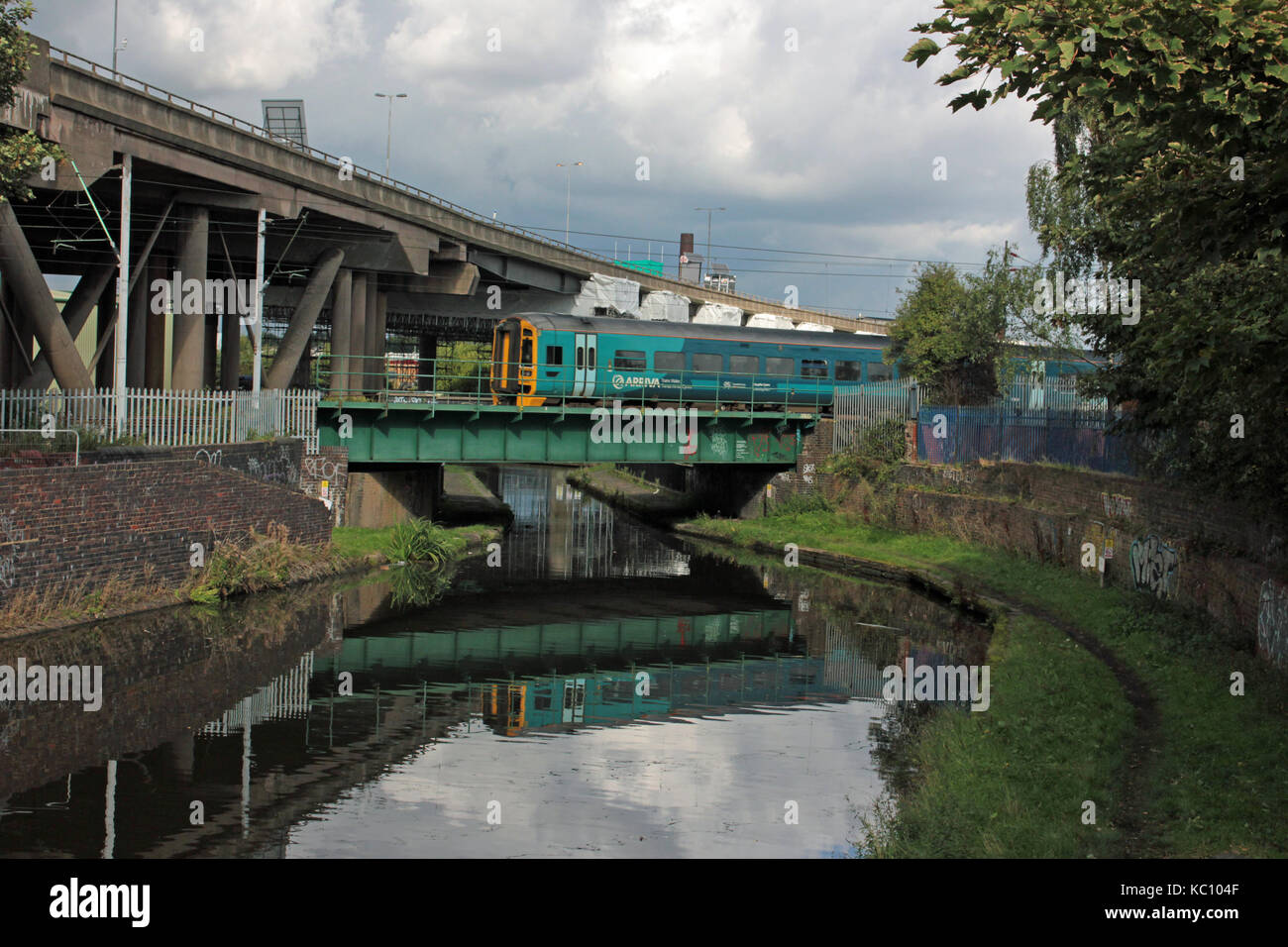 A Arriva Wales diesel multiple unit passenger train crosses a canal deep in the heart of the Black Country near - Stock Image