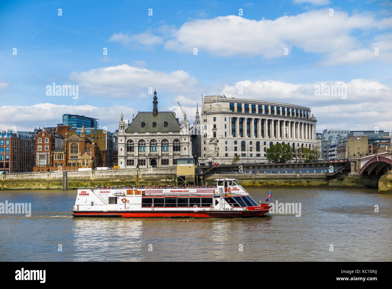 Red and white City Cruises tourist sightseeing boat cruises along the River Thames by Unilever House on Victoria - Stock Image