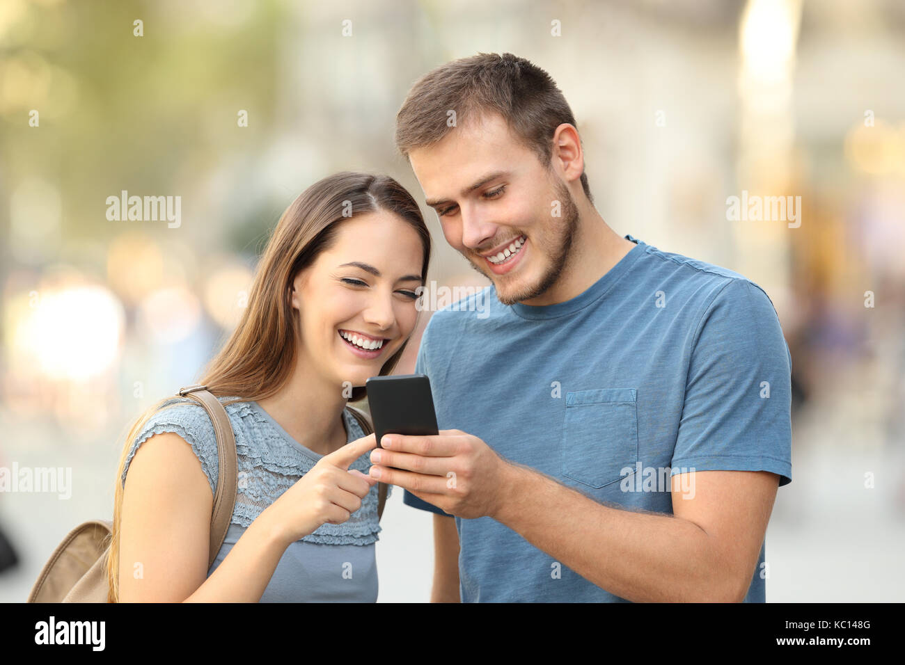 Happy couple searching on line content in a smart phone standing outdoors on the street - Stock Image