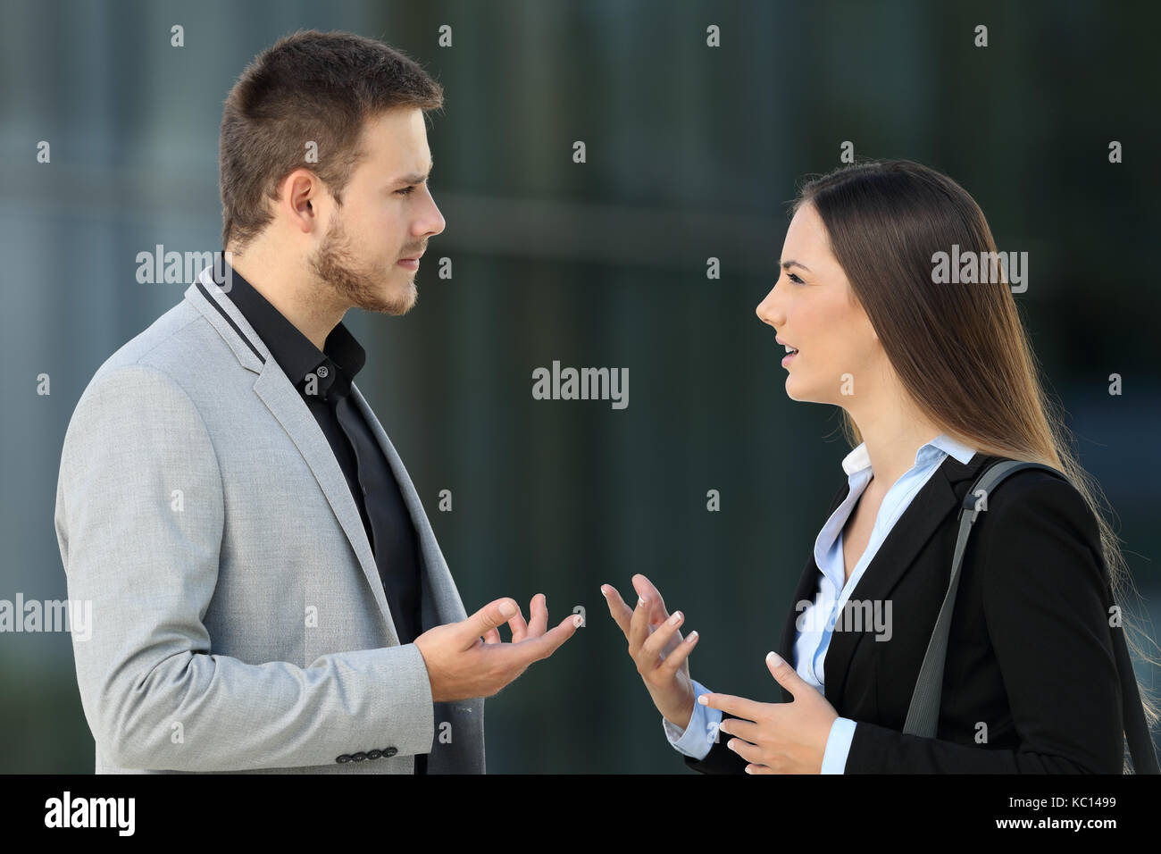 Side view portrait of two executives talking seriously standing outdoors on the street - Stock Image