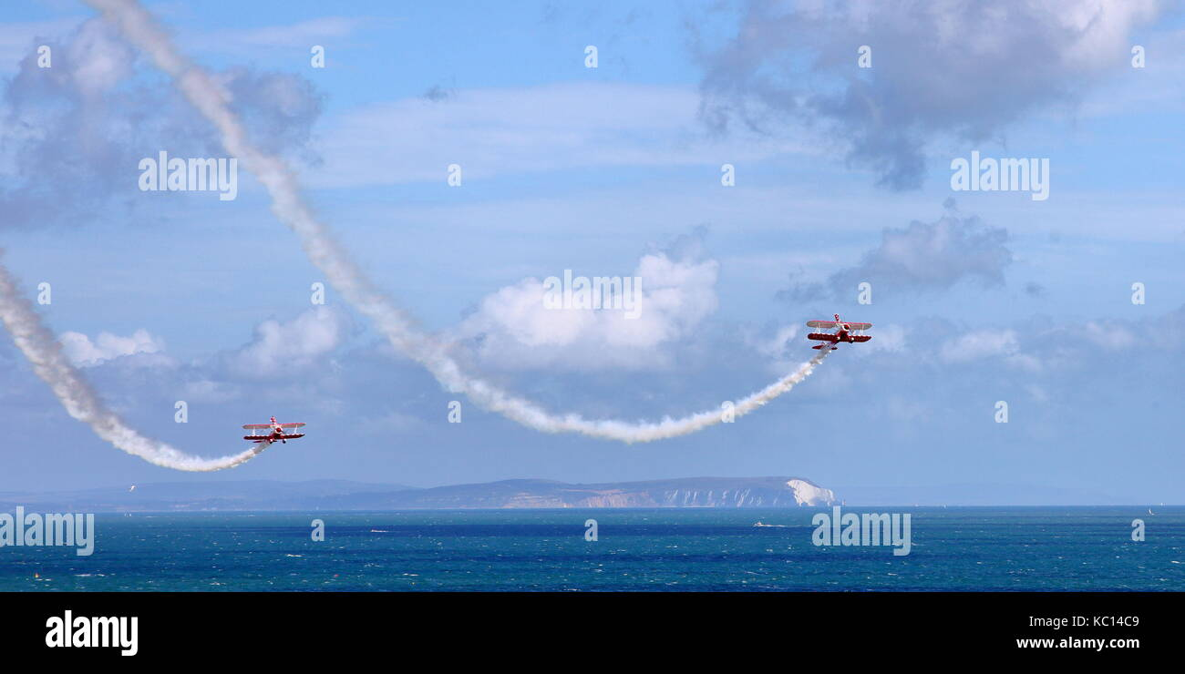Breitling / Guinot Wingwalkers in 2009 livery swoop down at the Bournemouth Air Festival with Solent, Isle of Wight - Stock Image