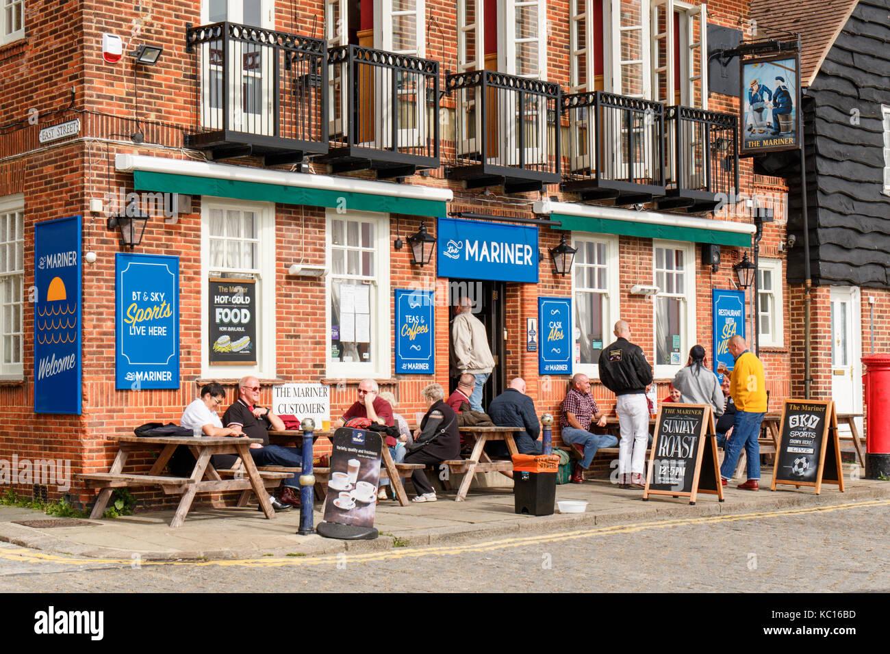 Adults enjoying drinking beer outside mariner pub, Folkestone horbour Kent UK - Stock Image