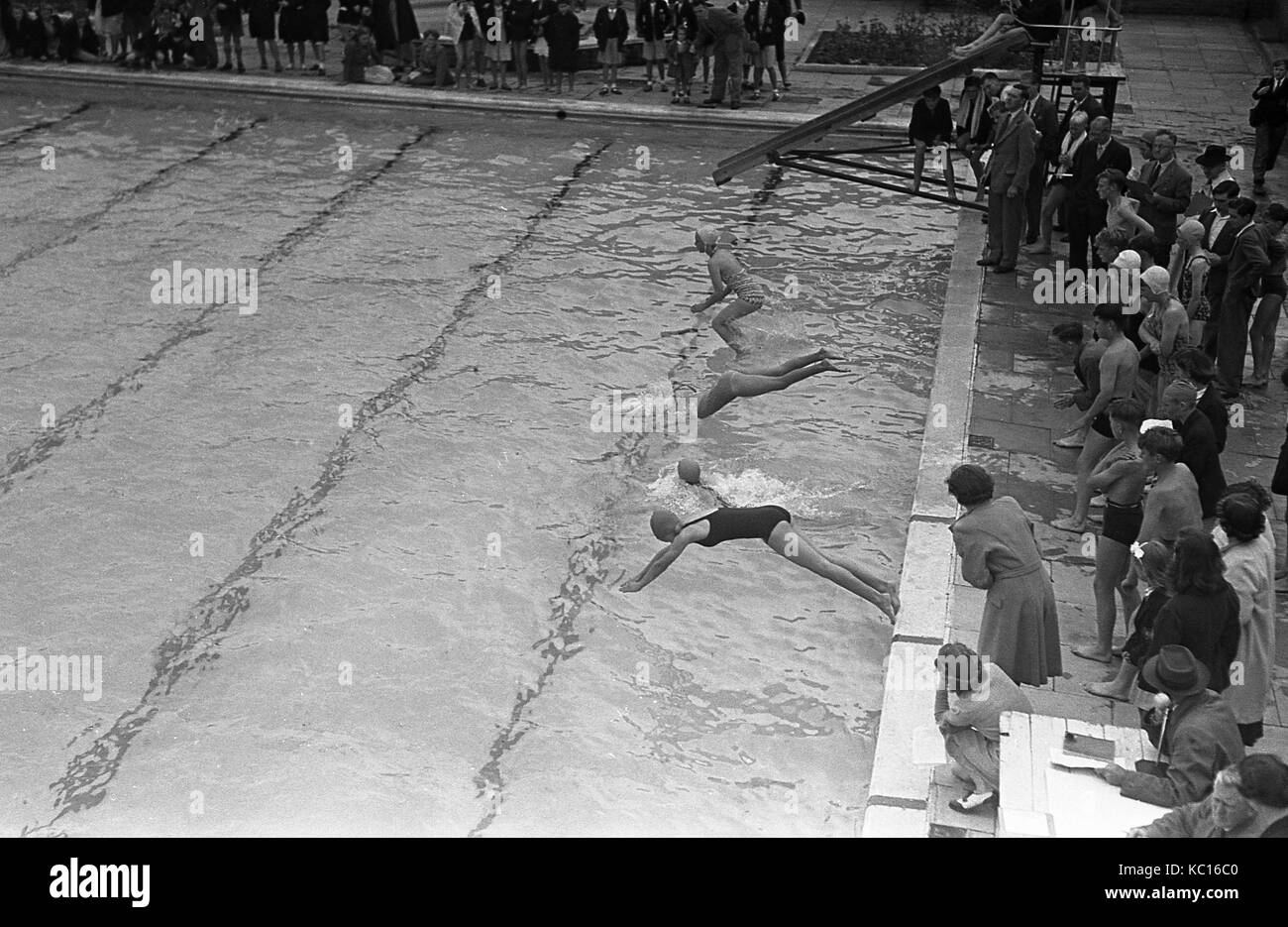 1950s, historical, young girls taking part in a swimming gala, with some diving in to start the race, others jumping - Stock Image