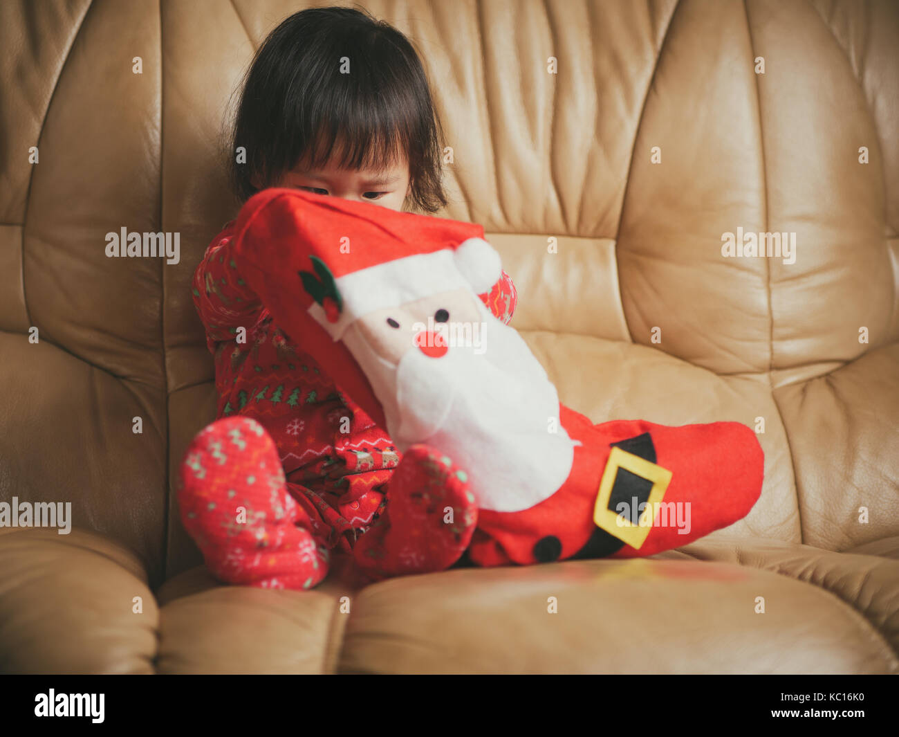 Baby girl looking for her gift in santa's sock on sofa - Stock Image