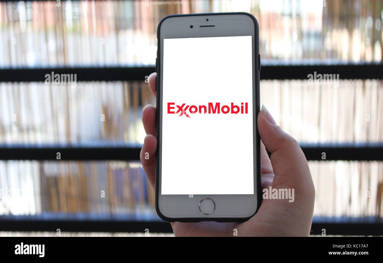 Consumer holding phone with ExxonMobil logo Stock Photo