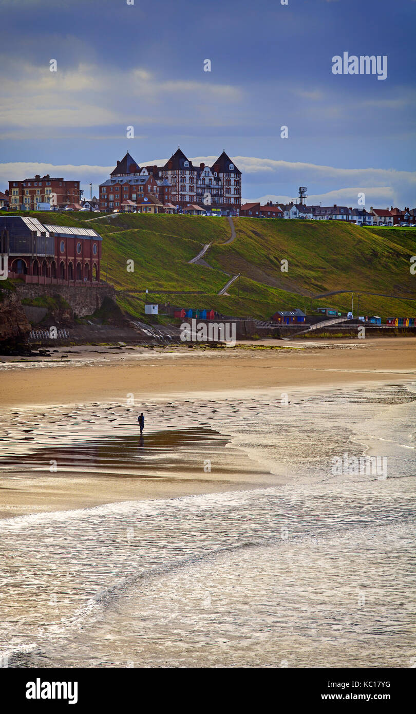 Solitary walker on the North Beach overlooked by the Metropole Luxury Apartments on the West Cliff area of Whitby, - Stock Image