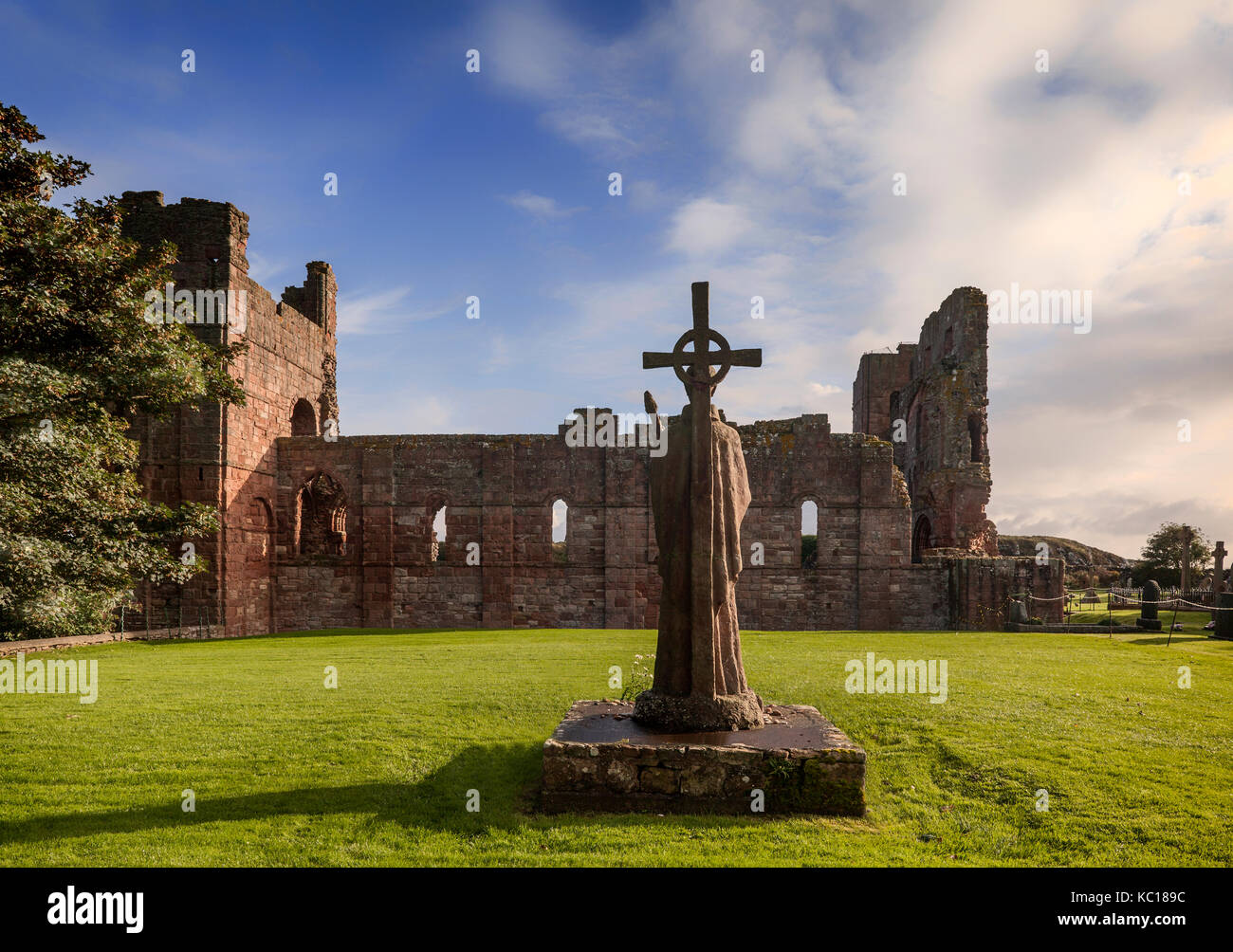 St Cuthbert's statue next the ruins of the church, built about 1150, on the spot where his body was buried. - Stock Image