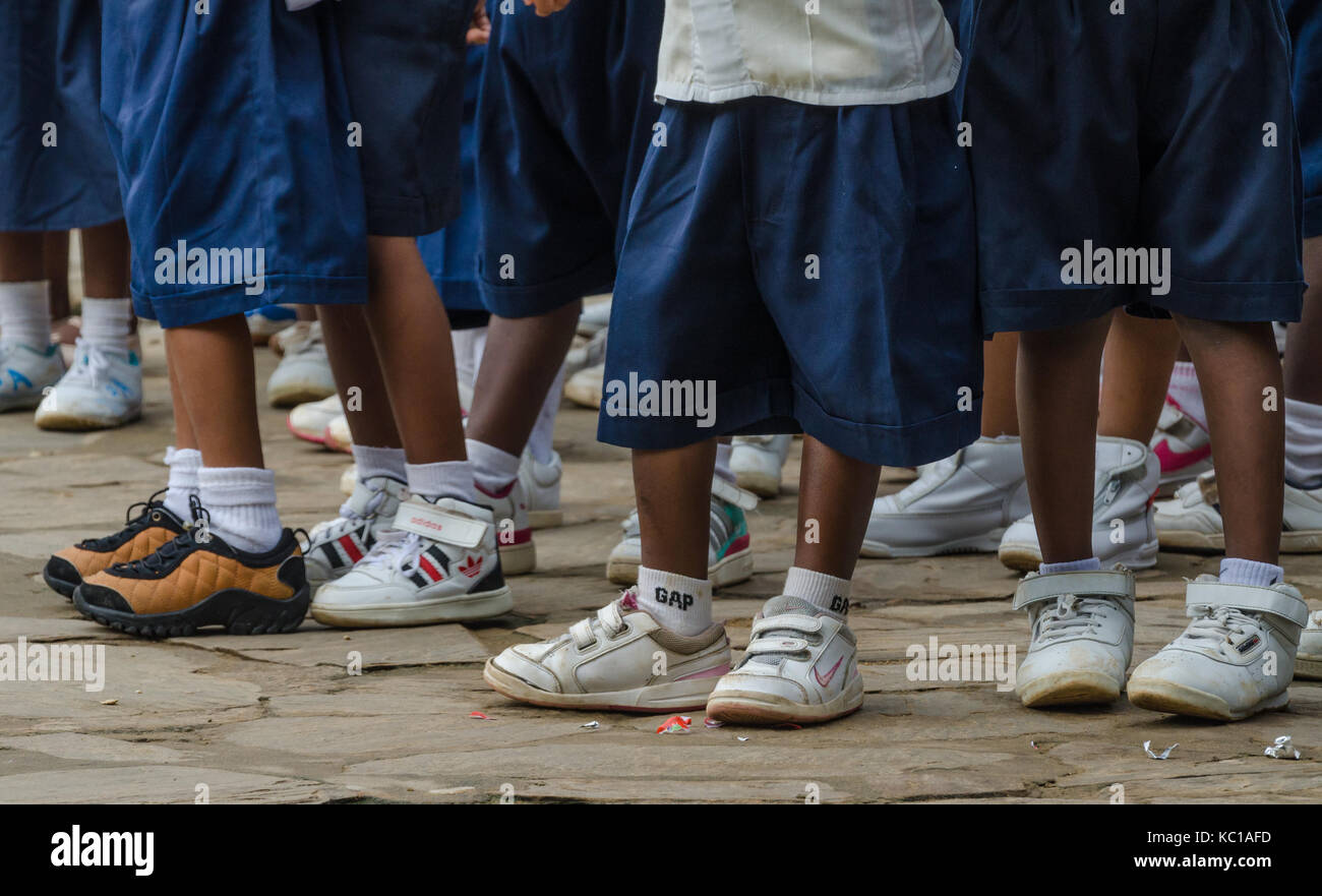 Legs with sneakers and school uniform pants of African pre school children, Matadi, Congo, Central Africa - Stock Image