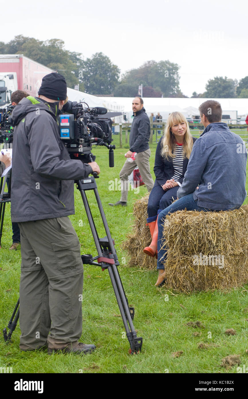 Camera man filming  Sarah cox interviewing sitting on hay bales - Stock Image