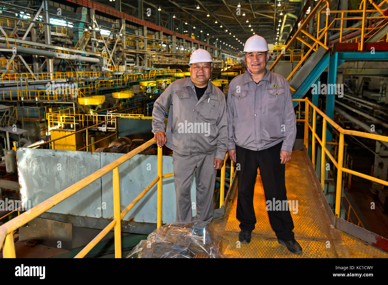 Two engineers on a factory floor for the extraction of copper from copper ore, Erdenet Mining Corporation EMC, Erdenet - Stock Image
