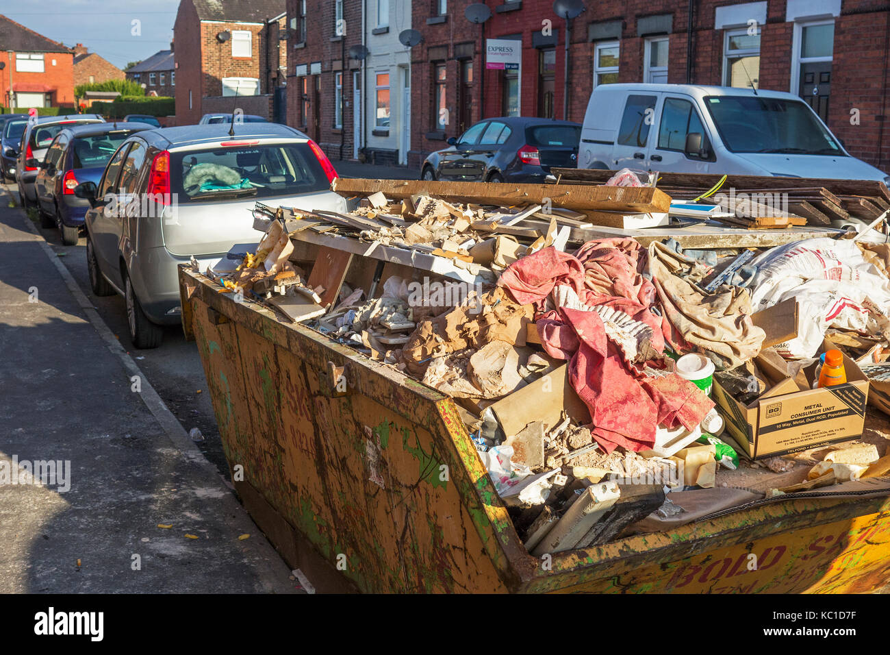 a full builders skip in a residential street, the north of england, - Stock Image