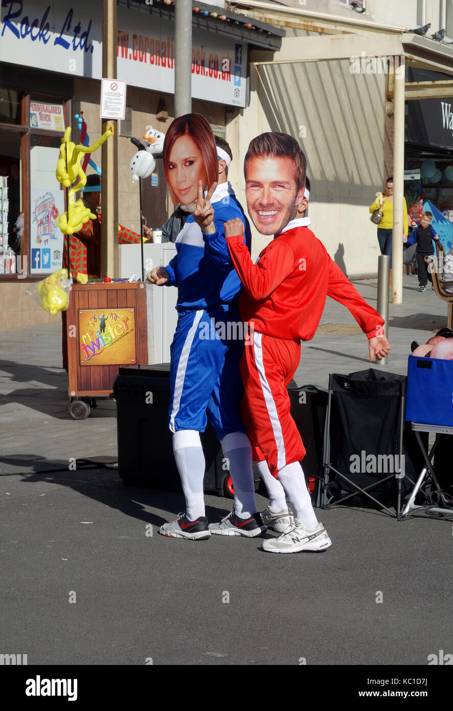 street entertainers imitating posh and becks wearing face masks. - Stock Image