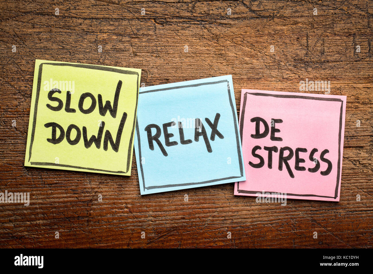 slow down, relax, de-stress concept -  motivational lifestyle reminders on colorful sticky notes against rustic - Stock Image
