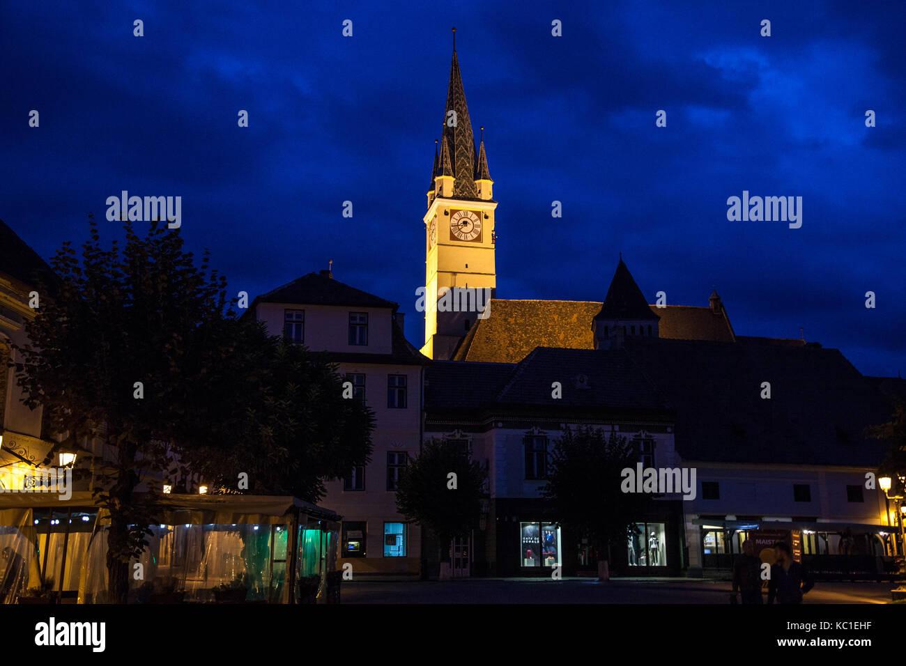 MEDIAS, ROMANIA - SEPTEMBER 22, 2017: Saint Margaret (Sf. Margareta) church in the evening seen from the main square - Stock Image