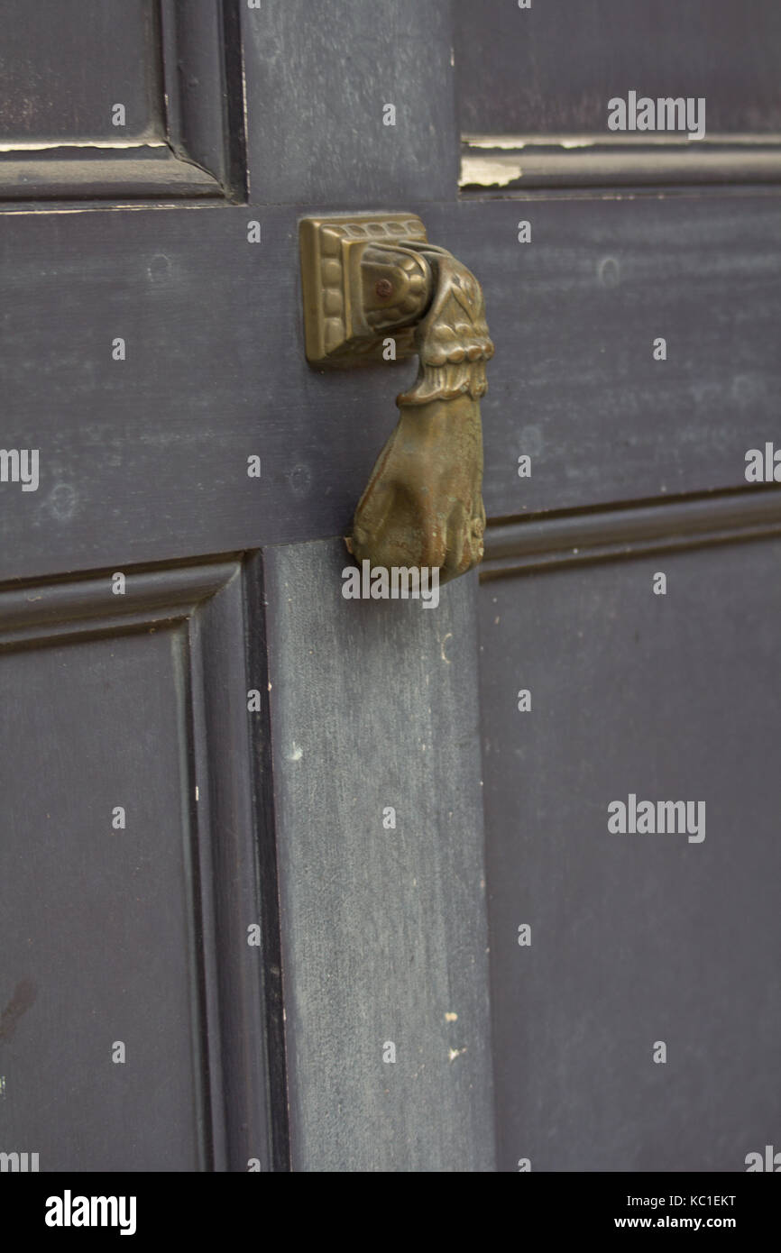 Small brass hand shaped door knocker on a grey door in the French Quarter, New Orleans. - Stock Image