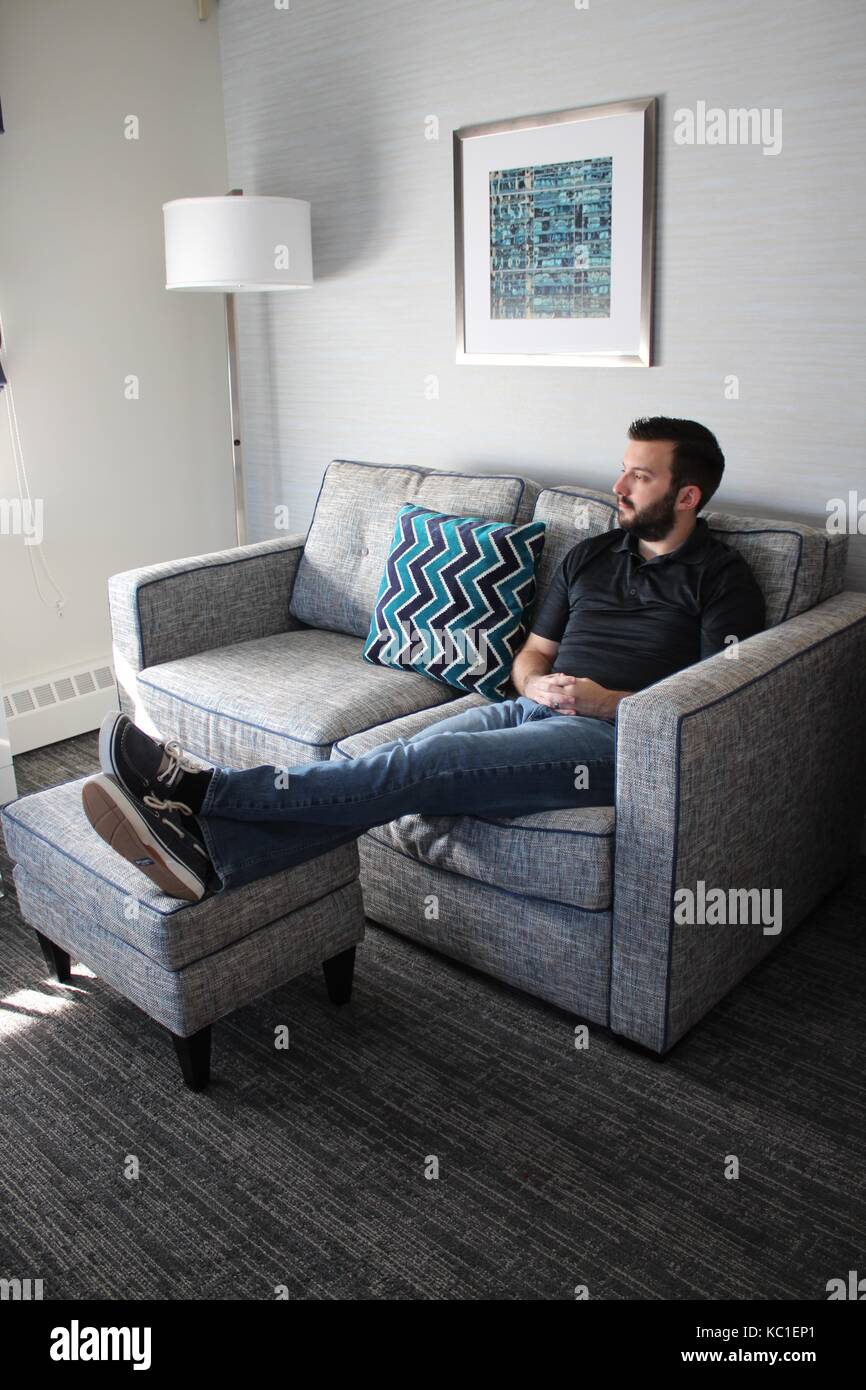 Man on Sofa Thinking and Relaxing - Stock Image
