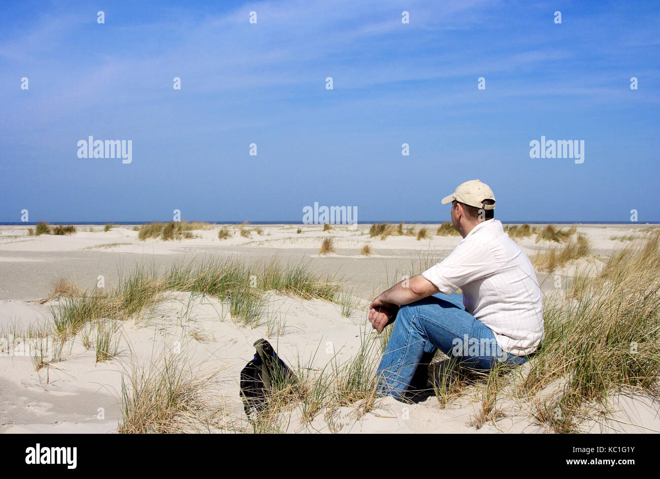 Man is sitting in the dunes, Nordeney, Germany. - Stock Image