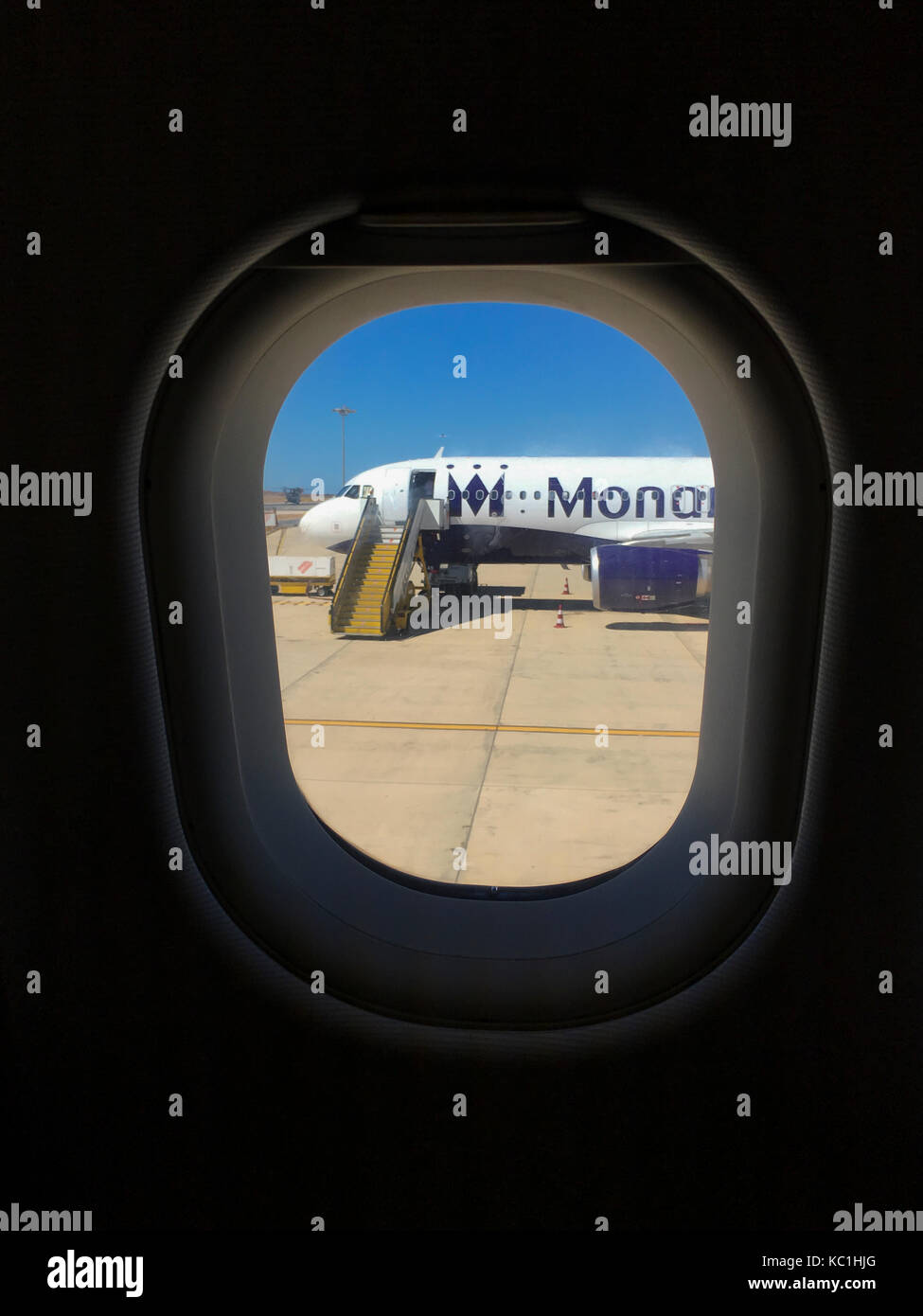 A deserted Monarch plane sits on the tarmac at Faro Airport, Portugal. Seen through the window of a neighbouring Stock Photo