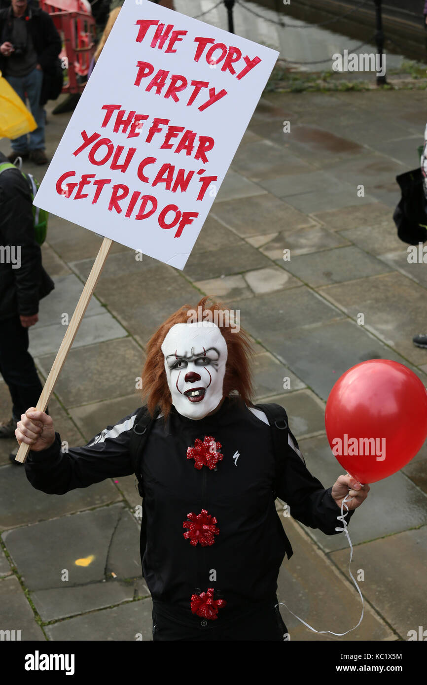 Manchester, UK. 1st October, 2017. A campaigner wearing a clown mask holding a placard which reads 'The Tory - Stock Image