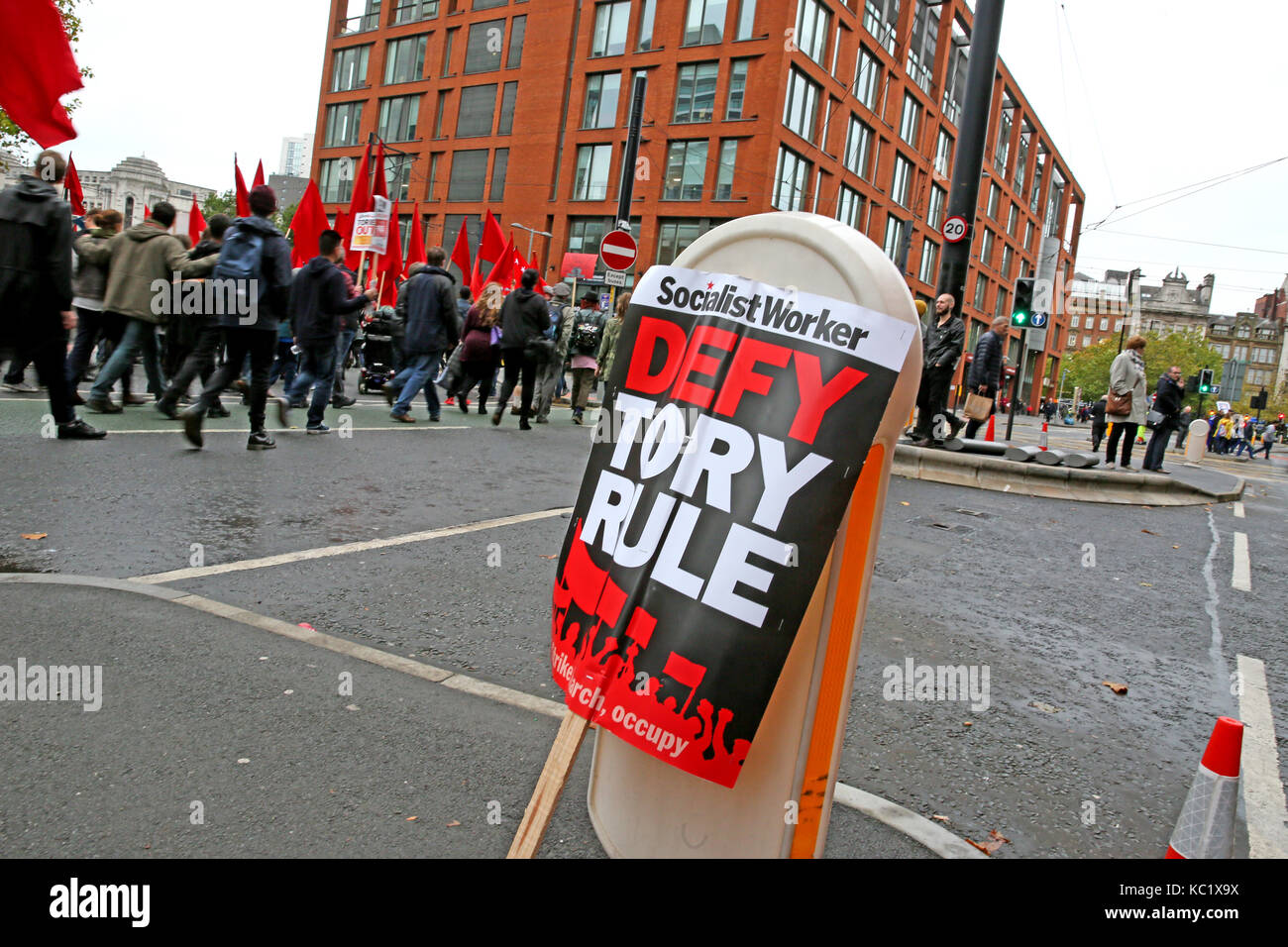 Manchester, UK. 1st October, 2017. A placard which reads 'Defy Tory Rule' leant on a street sign as an anti - Stock Image