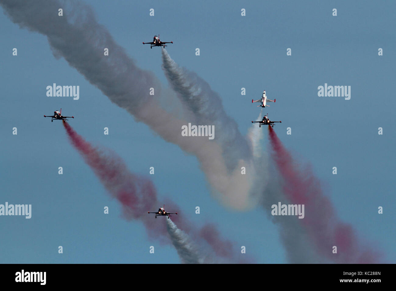 Display by the Turkish Stars aerobatic team of the Turkish Air Force. One aircraft flies head on through a slow - Stock Image