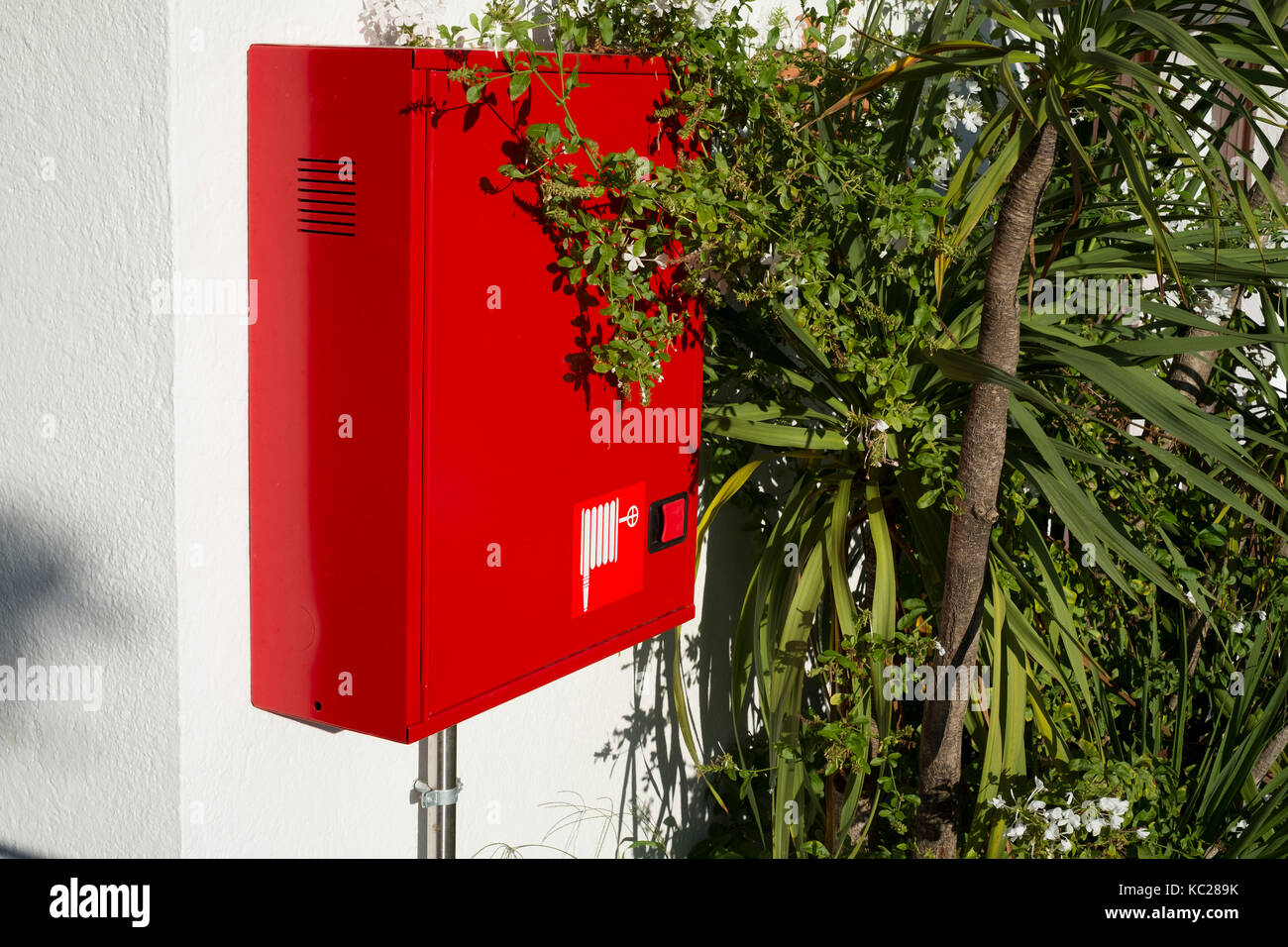 Red fire hose against green shrubbery in Lloret de Mar, Spain Stock Photo