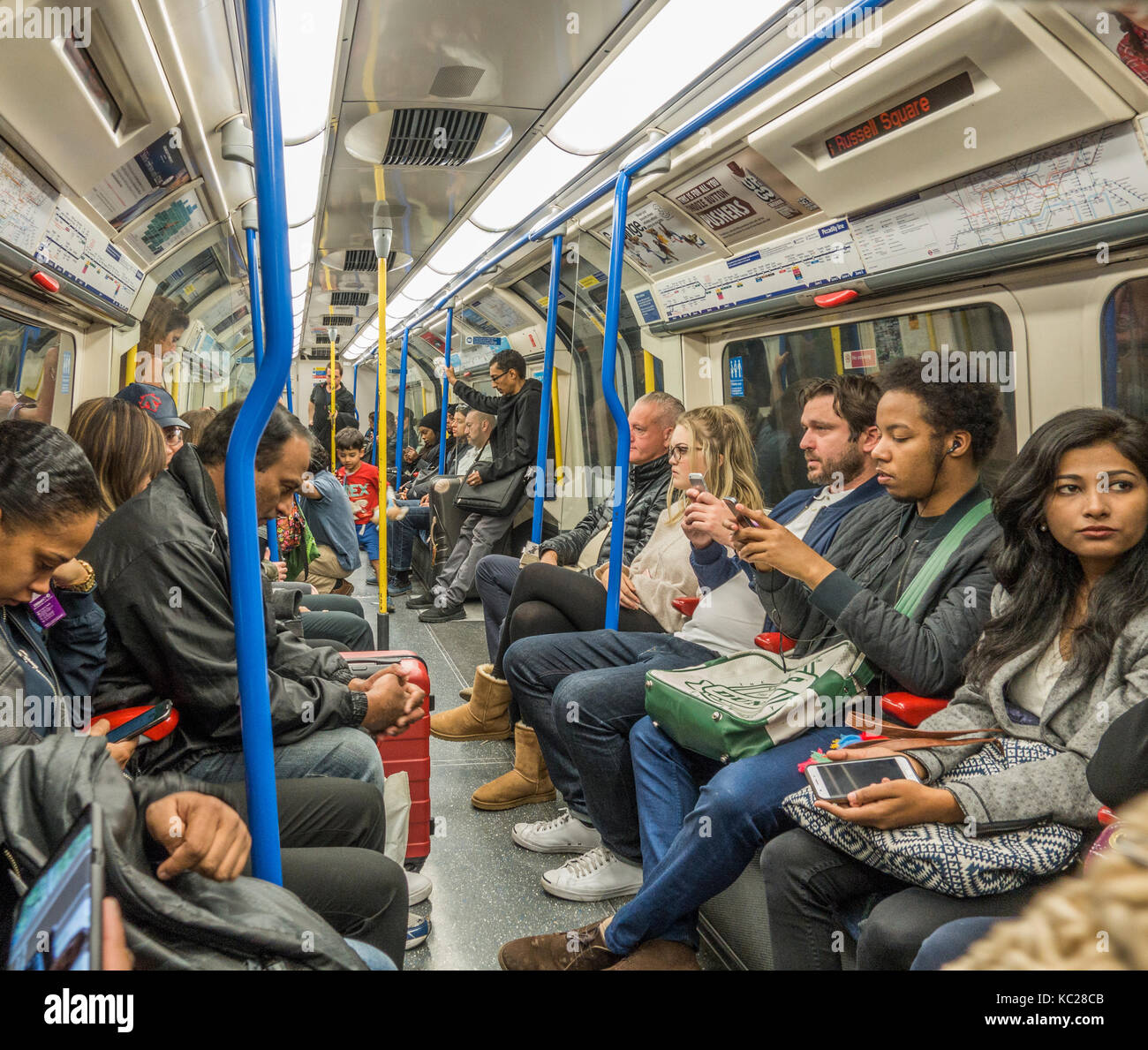 London Underground tube train - passengers / commuters sitting inside a busy Piccadilly Line carriage, during the - Stock Image