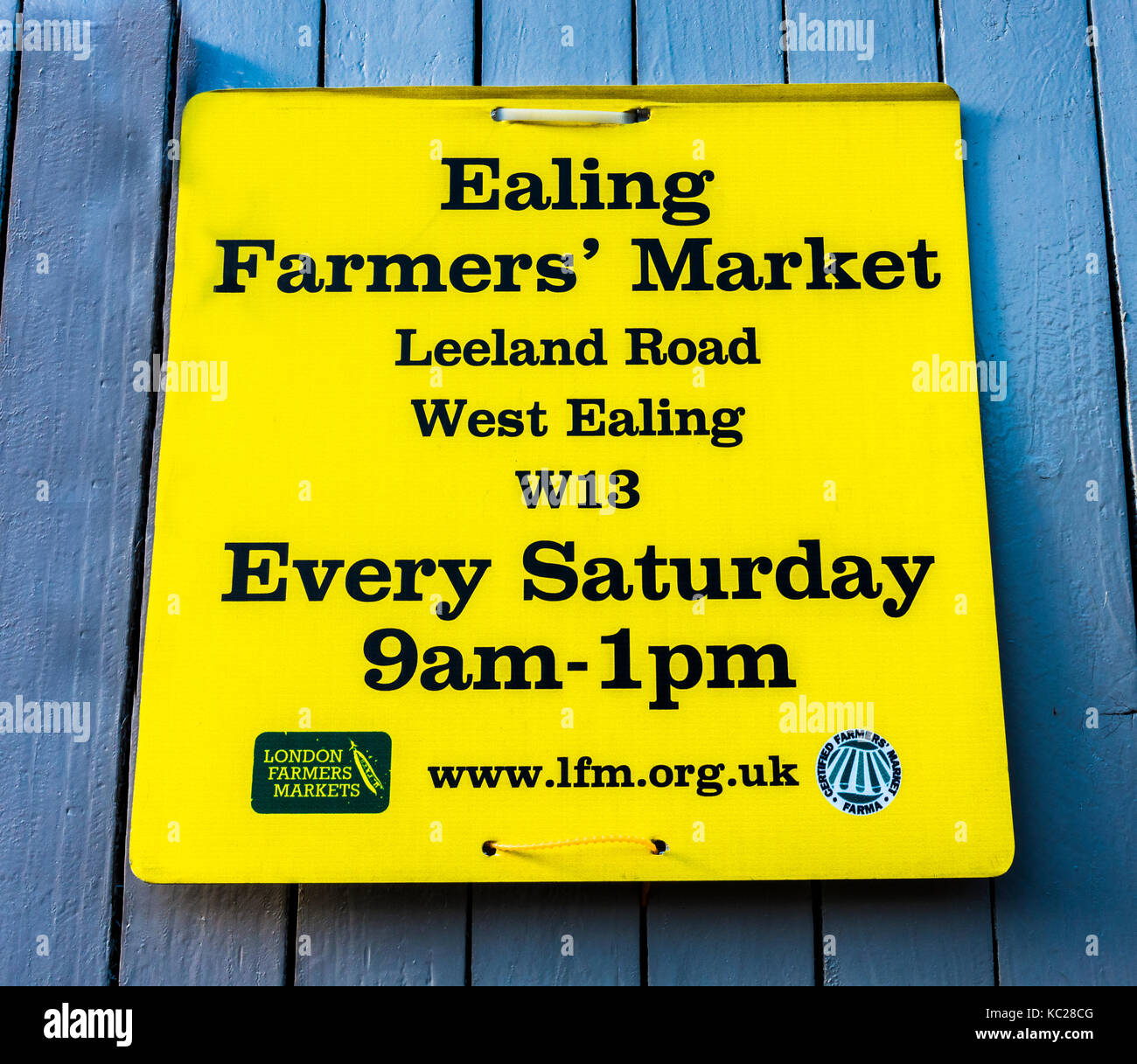 Ealing Farmers' Market in London W13, prominent yellow sign attached to a wooden fence in South Ealing, London - Stock Image