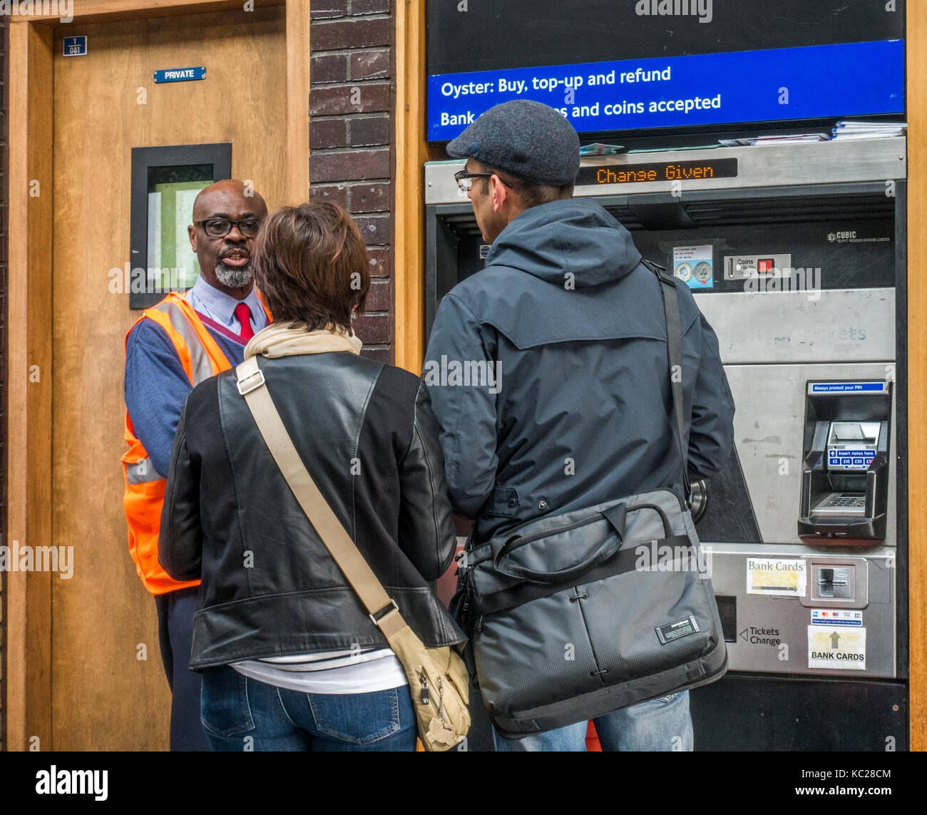 London Underground helpful assistant advising two people buying tickets at South Ealing tube station, London W5, - Stock Image