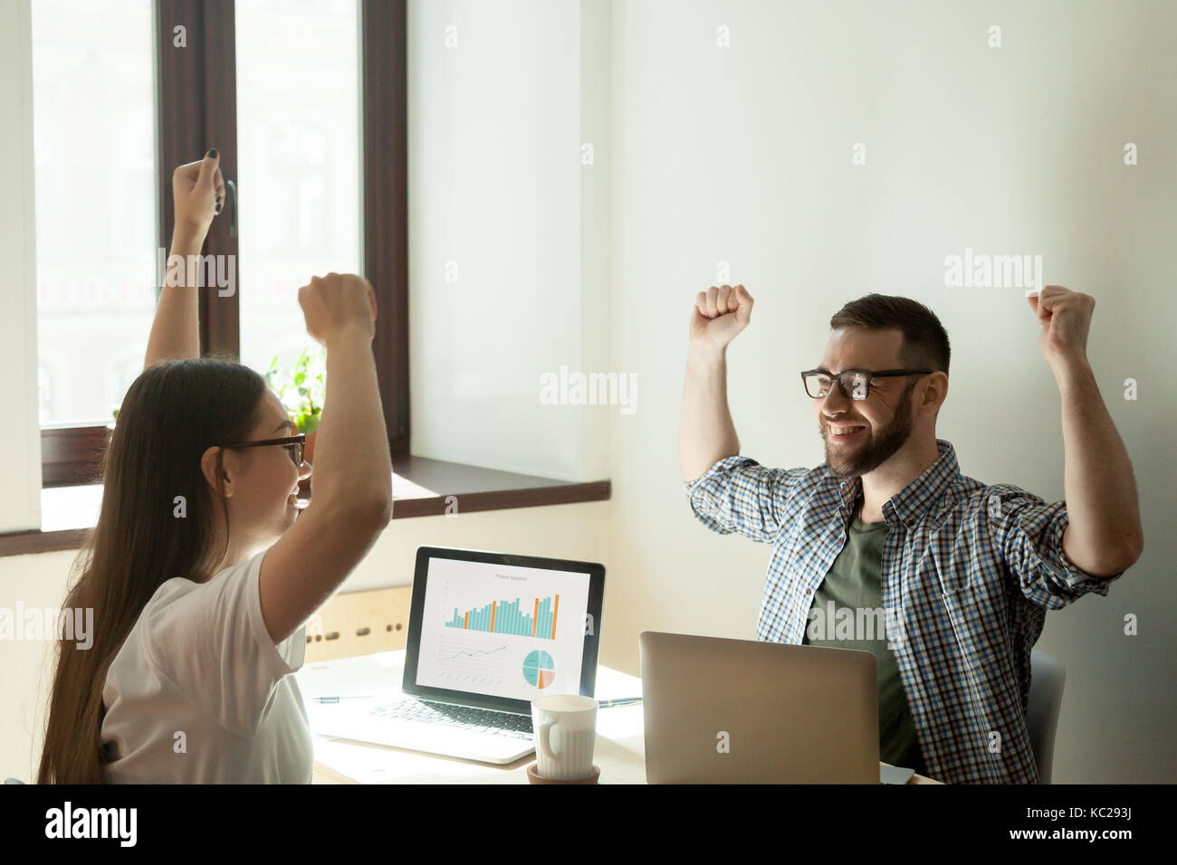 Finding a solution concept. Two businesspeople rising arms in winning gesture, rising stats on their laptop. - Stock Image