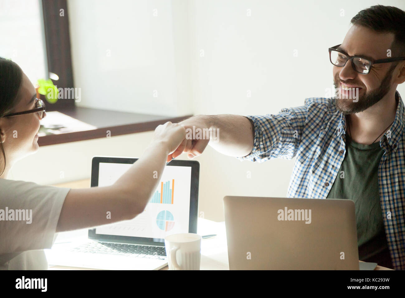 Celebrating job well done. Two businesspeople fist bumping in winning gesture, rising stats on their laptop. - Stock Image