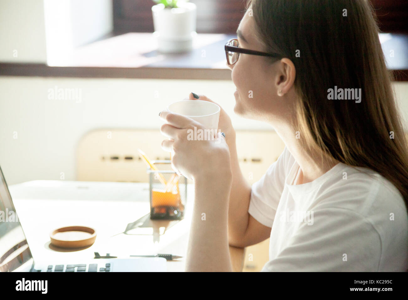 Female employee taking a break from work on laptop computer, enjoying a cup of tea or coffee at workplace desk in - Stock Image