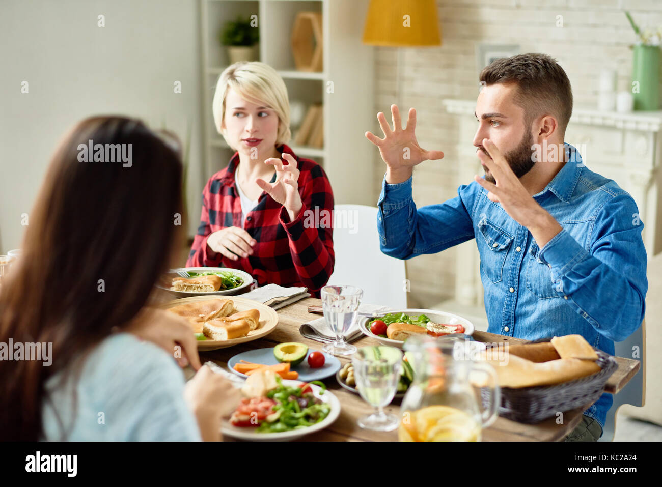 Portrait of young friends enjoying dinner together and big festive table and telling stories gesturing actively - Stock Image