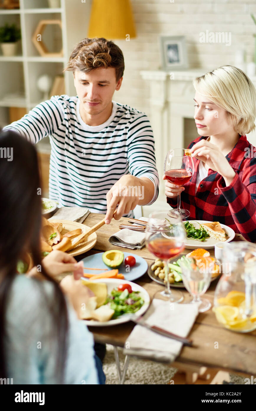 Group portrait of  young friends having dinner together, gathered at big table with delicious dishes on it - Stock Image