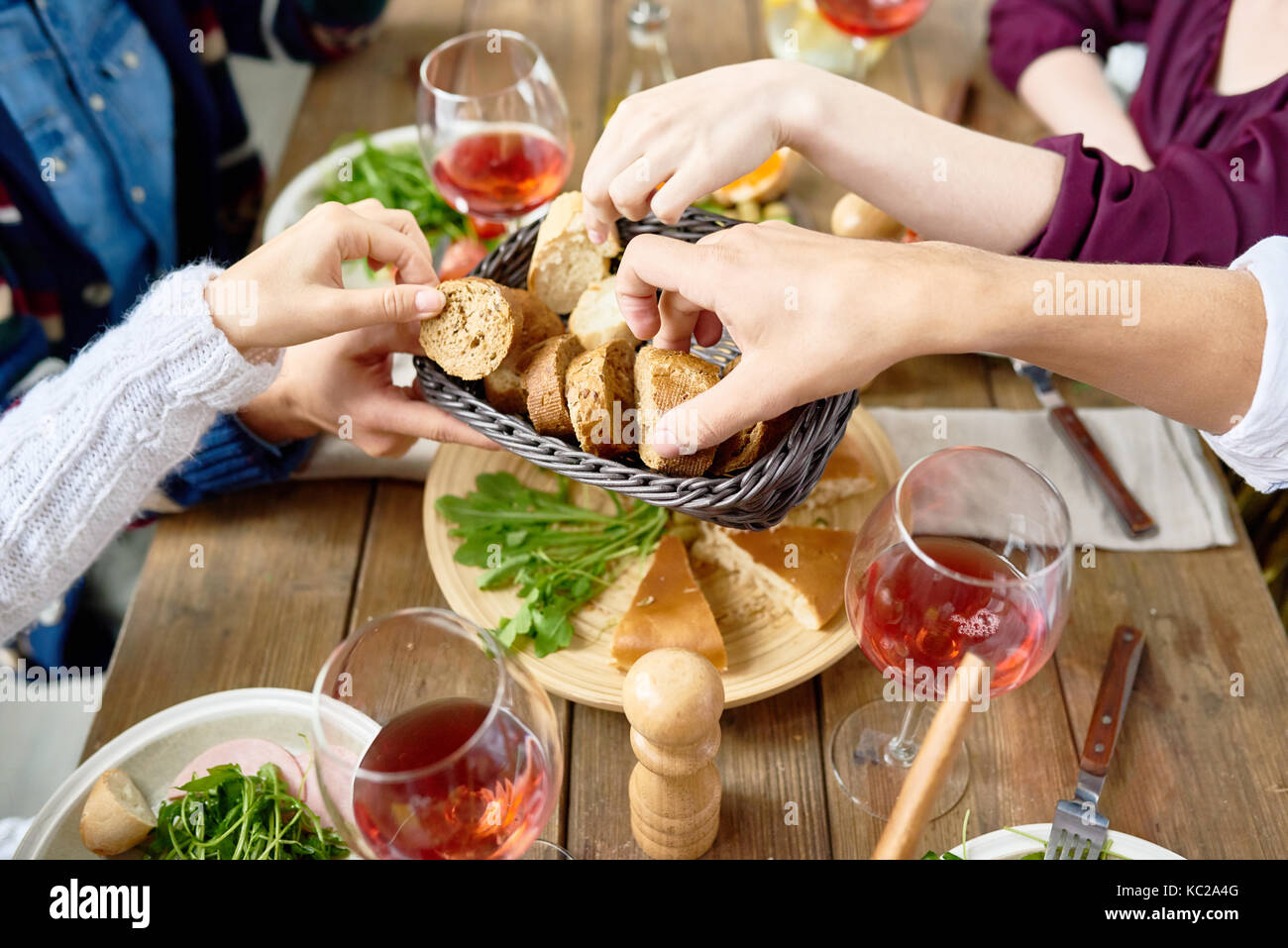 Closeup of unrecognizable people passing bread basket around at festive dinner table - Stock Image