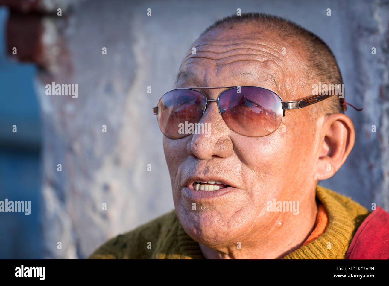 Buddhist monk with sunglasses which reflects Boudhanath stupa, Boudnath, Kathmandu, Nepal, South Asia - Stock Image