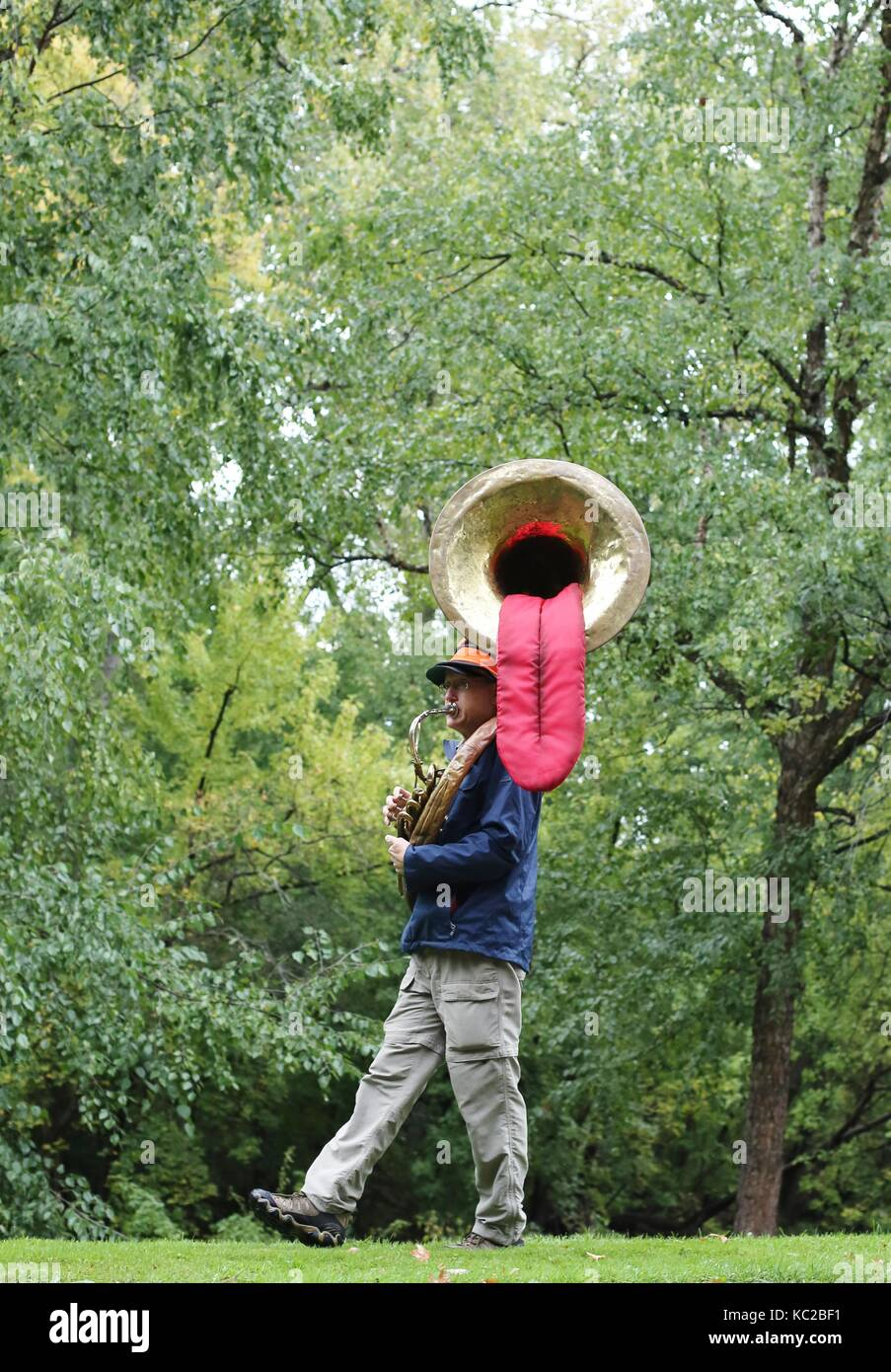 A man playing a tuba with a tongue hanging out of it, at the Twin Cities Marathon in Minneapolis, MN, USA. - Stock Image