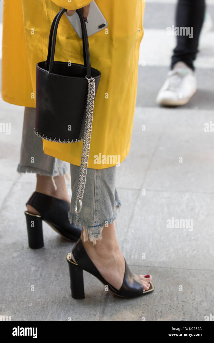 Milan, Italy - September 22, 2017: Model wearing a black handbag and a yellow overcoat during the Armani parade, - Stock Image