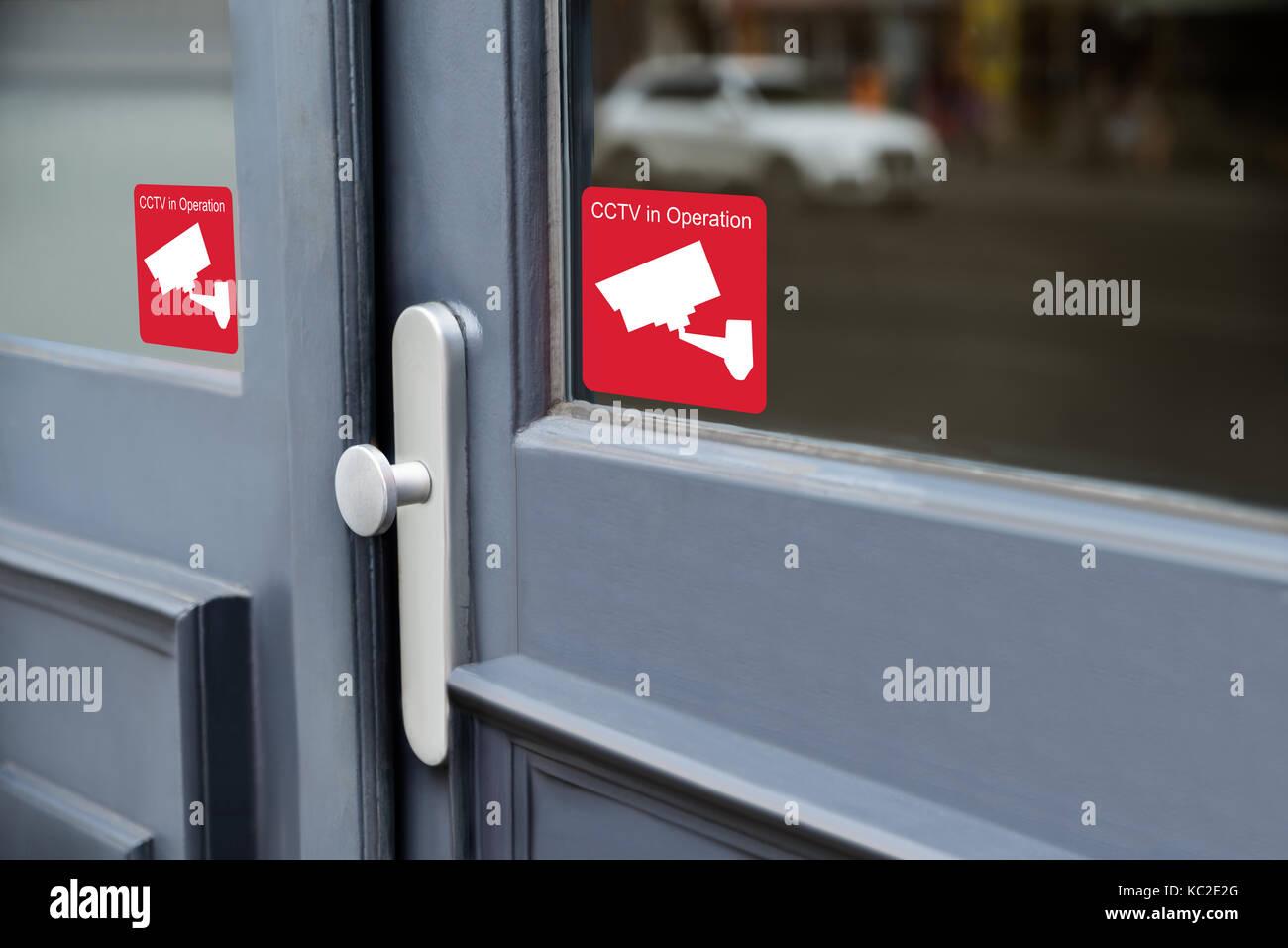 Close-up Of Warning Sticker Of Security Alarm Cctv Camera On Door - Stock Image