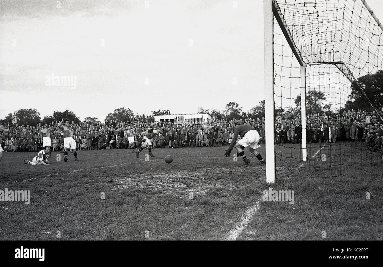 1960s, historical, semi-professional football match, goalmouth action, player dives and heads the ball towards the - Stock Image