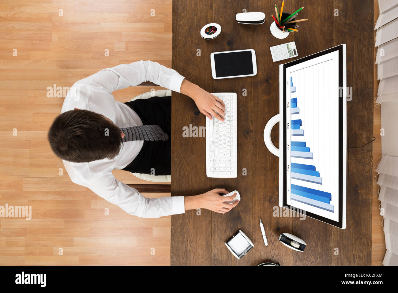 High Angle View Of Businessperson Analyzing Statistical Graph On Computer At Wooden Desk - Stock Image